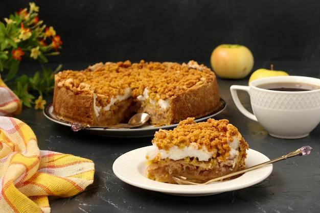 La torta con mele, meringhe e tazza di tè si trova su un piatto su una superficie scura
