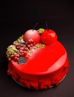 Torta con mousse di frutti di bosco nella glassa a specchio rosso decorata con un biscotto molecolare. sullo sfondo nero