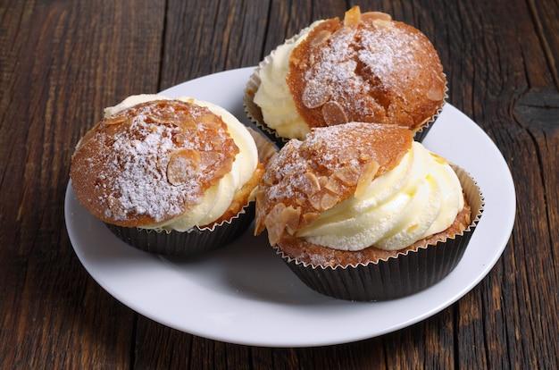 Torta con crema di burro e mandorle in piastra su tavola di legno