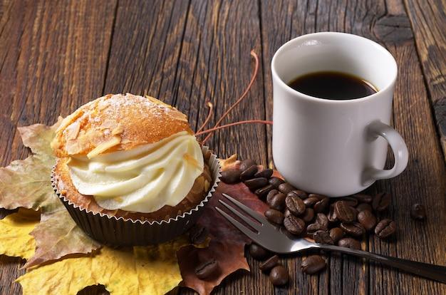 Torta con crema al burro e tazza di caffè su tavola di legno