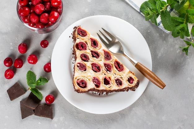 Torta con ciliegie, panna e cioccolato su un piatto bianco su sfondo chiaro