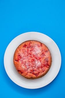 Torta con frutta sul piatto bianco su fondo in ceramica