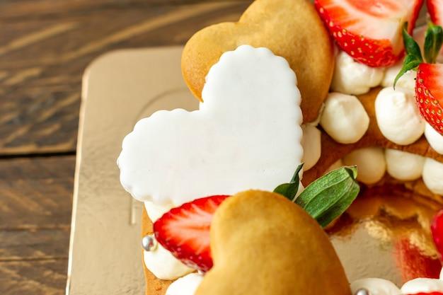 Torta con fragole, barrette di cioccolato al latte rosa, confettini d'argento, crema alla vaniglia e biscotti chape cuore da vicino.
