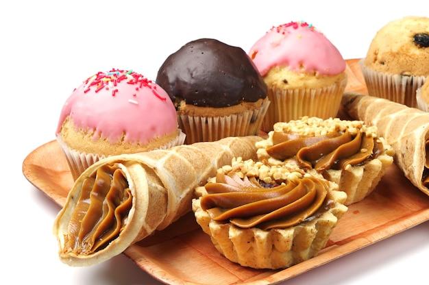 Torte e cupcakes su un piatto su bianco