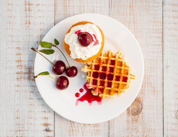 Torte con ciliegia su un piatto bianco su assi di legno