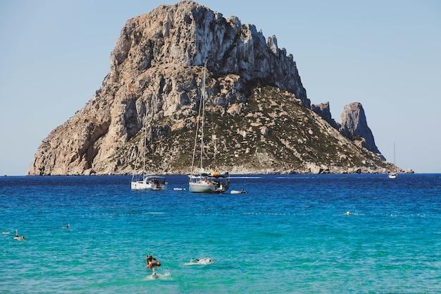 Spiaggia di cala hort con barche a vela sul mare e la montagna es vedra. ibiza, isole baleari, spagna