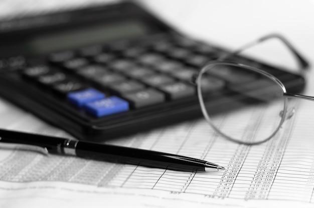 Calcolo dei numeri per la dichiarazione dei redditi con occhiali penna e calcolatrice