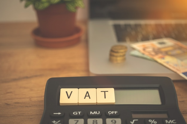 Calcolo delle tasse iva nell'unione europea. calcolatrice, parola iva e laptop con denaro sul desktop aziendale. foto del concetto di investimento e gestione
