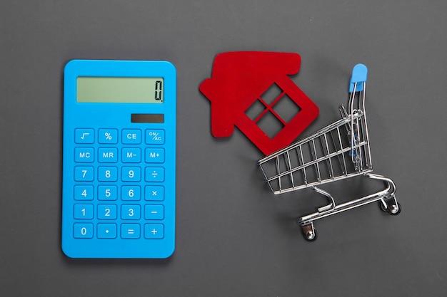 Calcolo del costo di acquisto o vendita di una casa. calcolatrice, figurina di una casa in un carrello della spesa su grigio. lay piatto