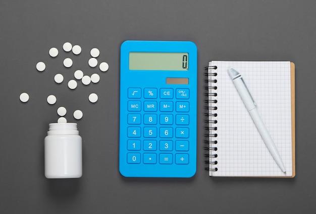 Calcolo del costo delle spese mediche. calcolatrice, taccuino e bottiglia di pillole su grigio.