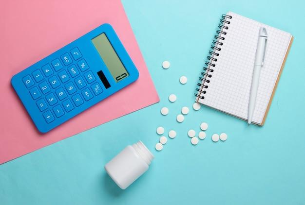 Calcolo del costo delle spese mediche. calcolatrice, taccuino e bottiglia di pillole su sfondo blu rosa. vista dall'alto. minimalismo