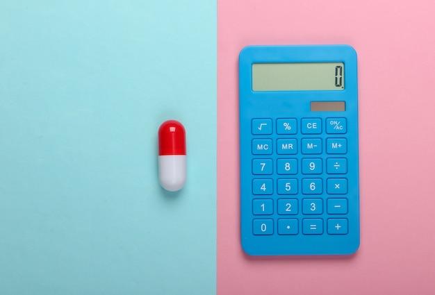 Calcolo del costo delle spese mediche. calcolatrice e pillola su uno sfondo pastello blu-rosa. vista dall'alto. minimalismo