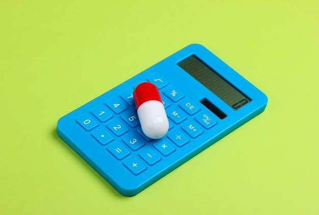 Calcolo del costo delle spese mediche. calcolatrice e pillola su sfondo verde.
