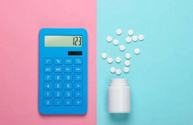 Calcolo del costo delle spese mediche. bottiglia di calcolatrice e pillole su sfondo blu-rosa pastello. vista dall'alto. minimalismo
