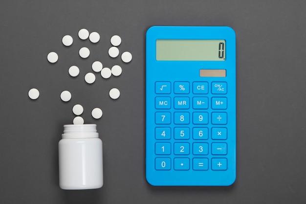 Calcolo del costo delle spese mediche. bottiglia di pillole e calcolatrice su grigio. minimalismo