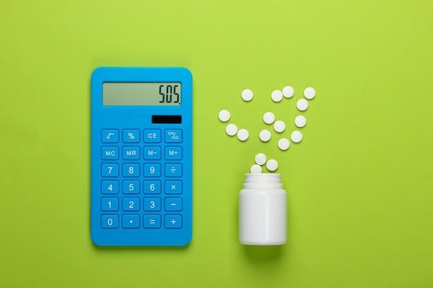 Calcolo del costo delle spese mediche. calcolatrice e bottiglia di pillole su sfondo verde. sos. vista dall'alto. minimalismo
