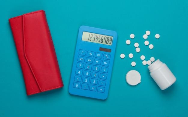 Calcolo del costo delle spese mediche. bottiglia di calcolatrice e pillole, portafoglio su sfondo blu. vista dall'alto. minimalismo