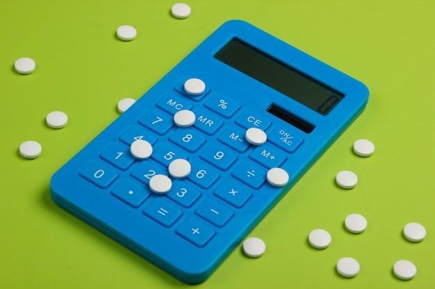 Calcolo del costo delle spese mediche. calcolatrice e pillole sul verde. minimalismo