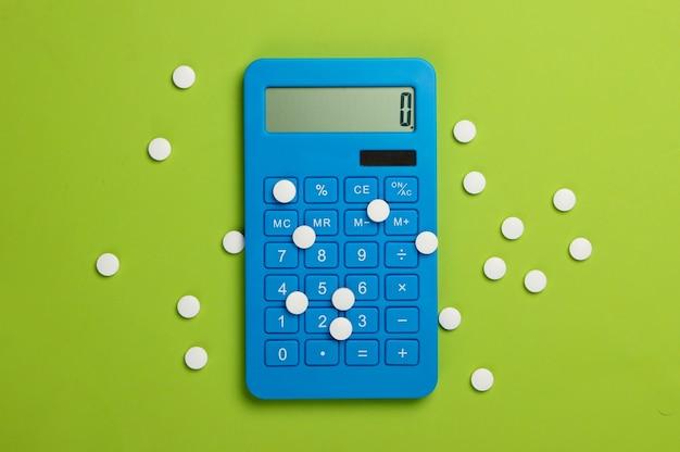 Calcolo del costo delle spese mediche. calcolatrice e pillole sul verde.