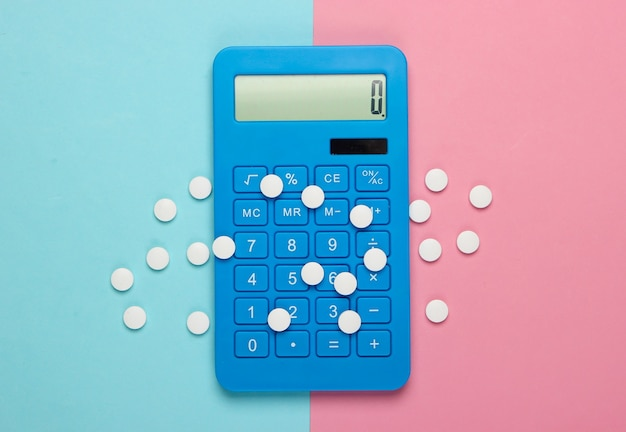 Calcolo del costo delle spese mediche. calcolatrice e pillole su pastello blu rosa. minimalismo