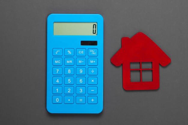 Calcolo del costo degli alloggi in affitto. figurina della casa rossa, calcolatrice su grigio