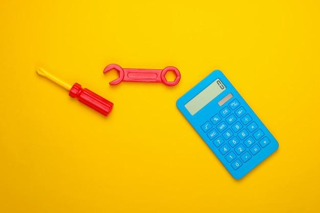Calcolo del costo dei lavori di riparazione. calcolatrice e chiave giocattolo e cacciavite su sfondo giallo. vista dall'alto