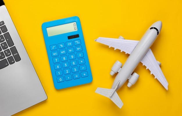 Calcolo del costo del turismo o dell'emigrazione. prenotazione online. computer portatile, aereo, calcolatrice su giallo