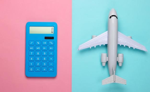 Calcolo del costo del viaggio, viaggio aereo o consegna aerea. calcolatrice con figura di aeroplano su sfondo rosa blu pastello. vista dall'alto