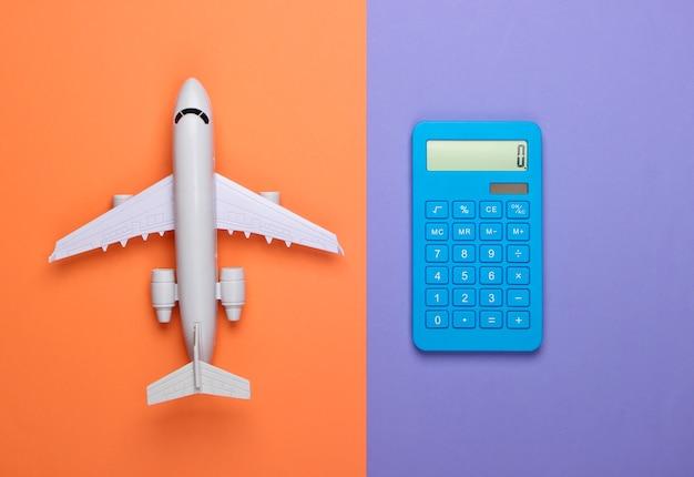 Calcolo del costo del viaggio, viaggio aereo o consegna aerea. calcolatrice con figura di aeroplano su sfondo viola-arancio. vista dall'alto