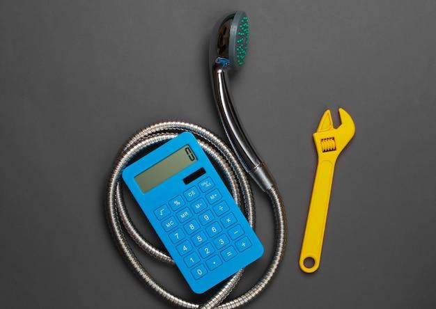 Calcolo dei costi per l'impianto idraulico. calcolatrice, soffione doccia con tubo flessibile, chiave inglese su grigio.