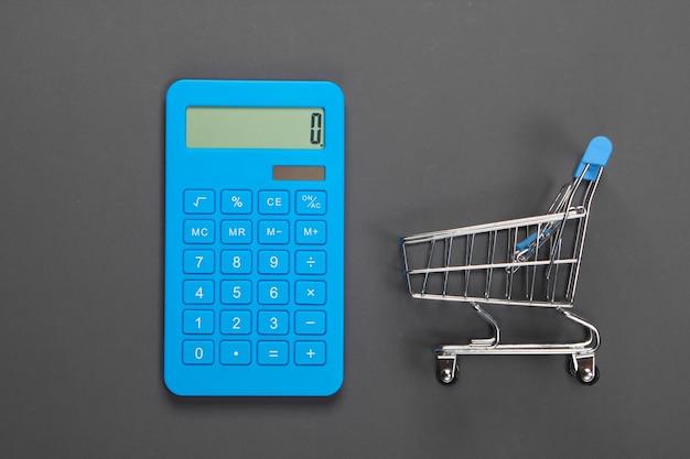 Calcolo dei costi per la spesa, acquisti al supermercato. calcolatrice e carrello della spesa su grigio. minimalismo