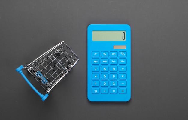 Calcolo dei costi per la spesa, acquisti al supermercato. calcolatrice e carrello della spesa su grigio