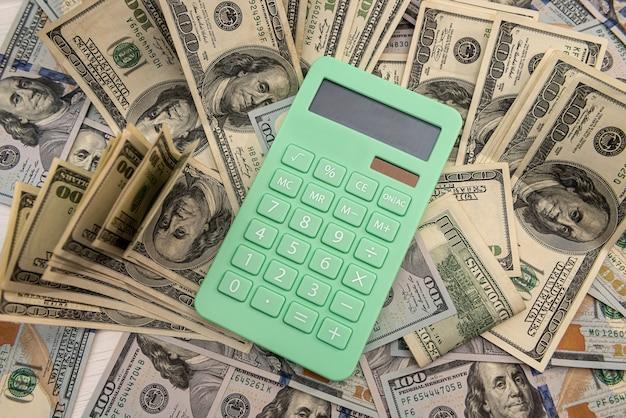 Calcolatrice e banconote da 100 dollari, concetto di risparmio