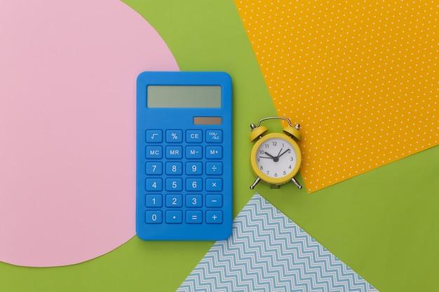 Calcolatrice e sveglia su sfondo di carta colorata creativa.