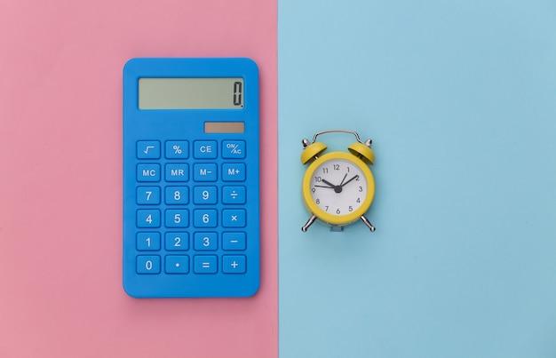 Calcolatrice e sveglia su sfondo rosa pastello blu.