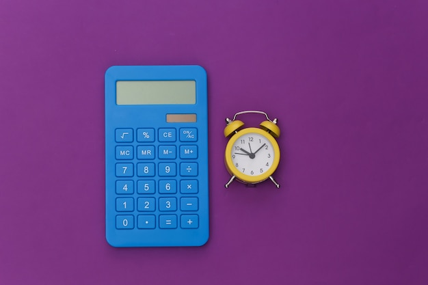 Calcolatrice e sveglia su sfondo viola.