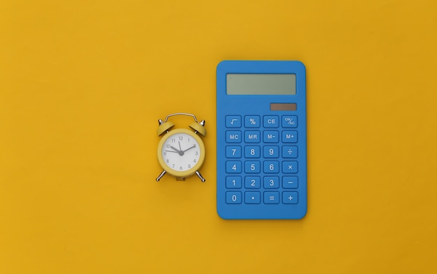 Calcolatrice e sveglia su sfondo giallo.
