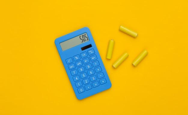 Calcolatrice e batterie su sfondo giallo. vista dall'alto