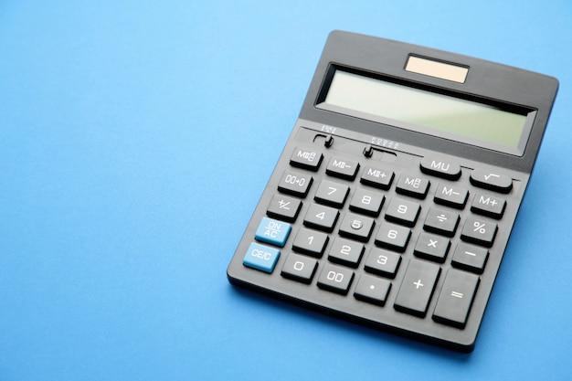 Calcolatrice su sfondo blu con spazio di copia