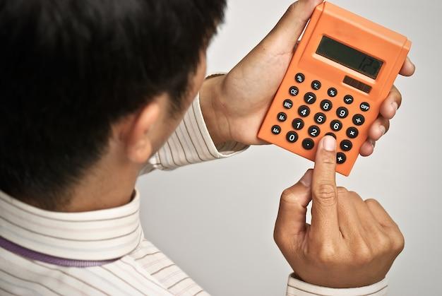 Calcolatrice sulla mano dell'uomo d'affari, concetto di affari della finanza.