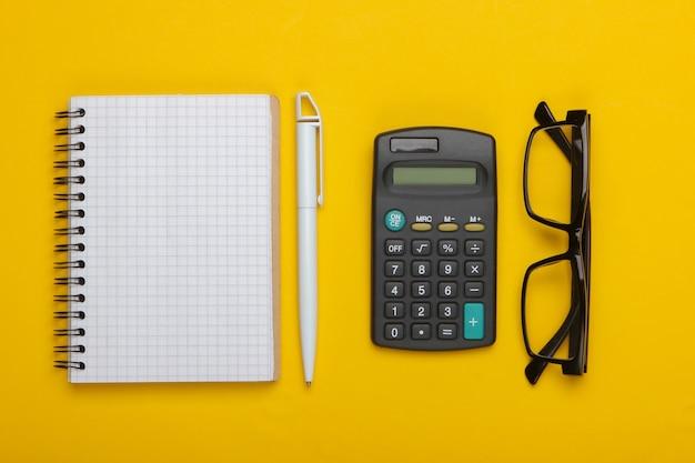 Calcolatrice e occhiali da vista classici, taccuino su un colore giallo.