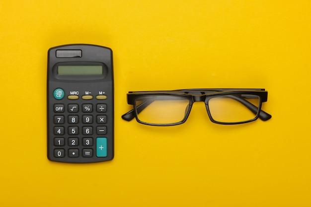 Calcolatrice e occhiali da vista classici su un giallo.