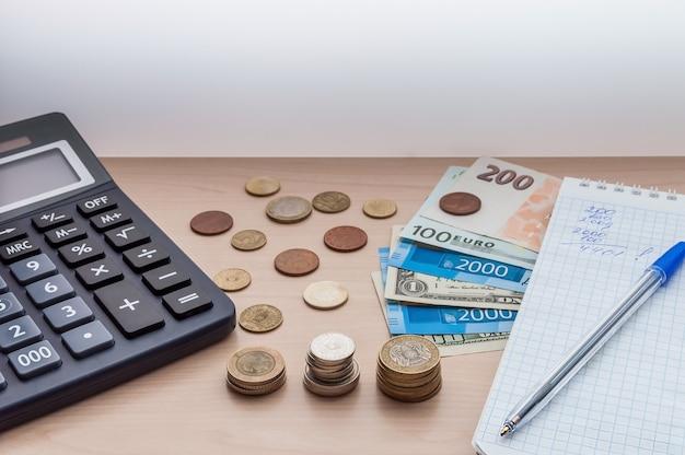 Calcolatrice, monete, banconote, denaro, un quaderno, una penna sulla scrivania