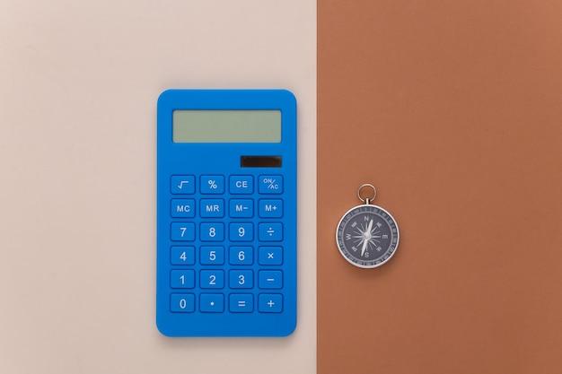 Calcolatrice e bussola su sfondo marrone beige. concetto di affari. vista dall'alto