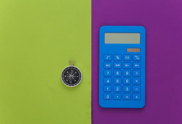Calcolatrice e bussola su sfondo verde viola. concetto di affari. vista dall'alto