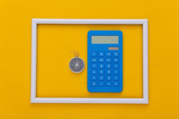 Calcolatrice e bussola in cornice bianca su sfondo giallo. concetto di affari. vista dall'alto