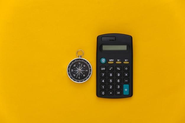 Calcolatrice e bussola su sfondo giallo. concetto di affari. vista dall'alto