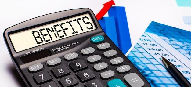 Sul display della calcolatrice c'è una scritta benefici. nelle vicinanze ci sono diagrammi e grafici colorati. concetto di affari