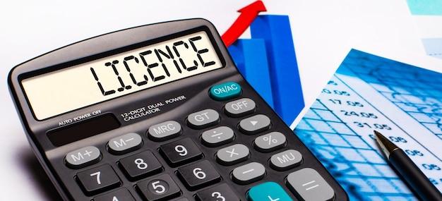 Sul display della calcolatrice è presente la scritta licence. nelle vicinanze ci sono diagrammi e grafici colorati. concetto di affari