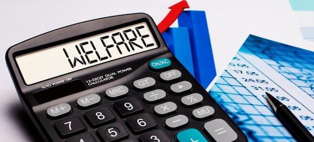 Sul display della calcolatrice è presente la scritta welfare. nelle vicinanze ci sono diagrammi e grafici colorati. concetto di affari